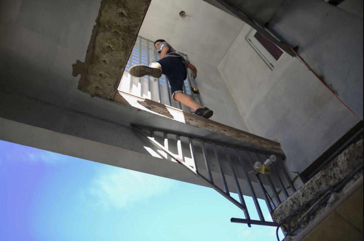 Un chico en el segundo piso de una casa semiderruida.