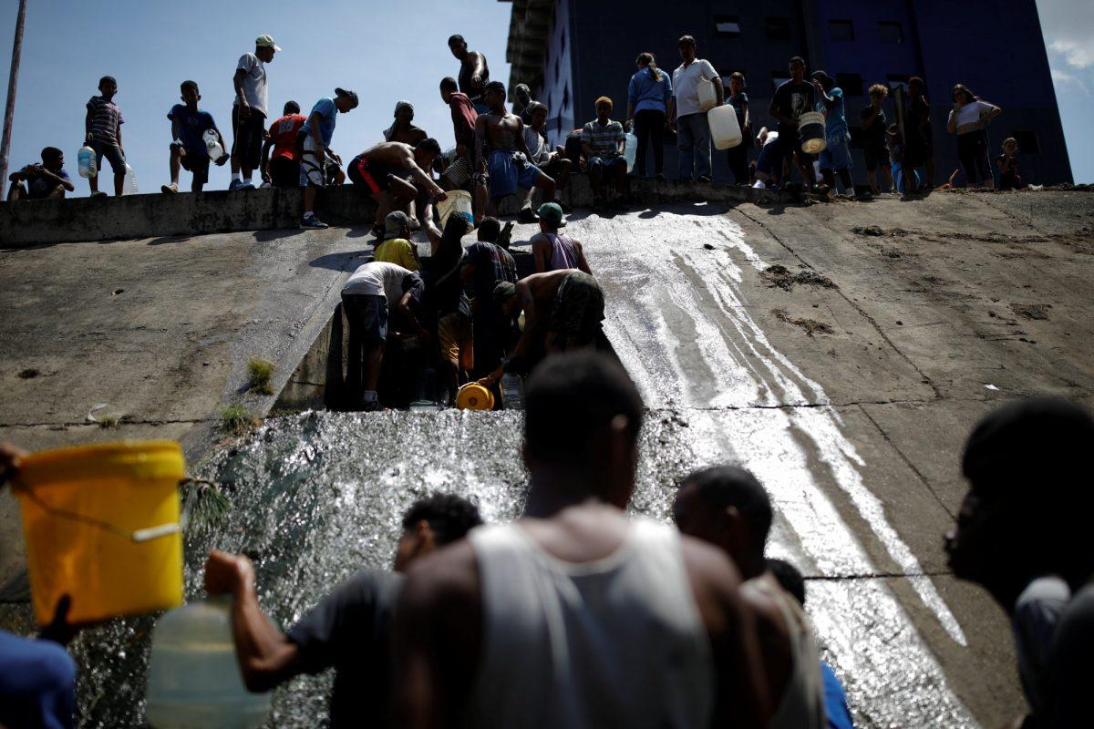 Muchas personas tuvieron que recolectar agua liberada a través de un drenaje de aguas residuales.
