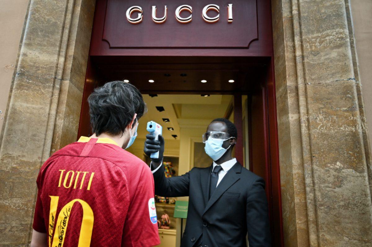 El empleado de una tienda de Gucci en Via dei Condotti, en Roma, mide la temperatura a un cliente (Foto: Alberto PIZZOLI/ AFP)