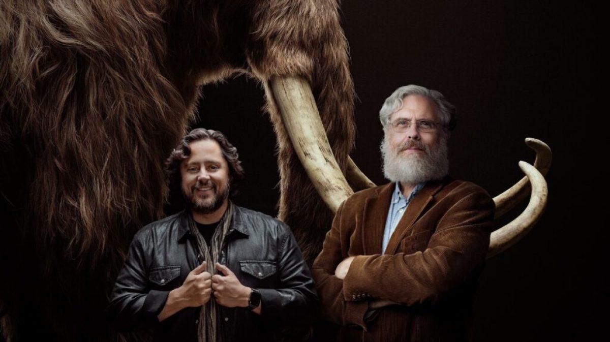 Fotografía cedida por la empresa Colossal donde aparecen sus cofundadores, los empresarios y científicos Ben Lamm (i) y George Church (d), mientras posan frente a la imagen de un mamut. - Foto: EFE