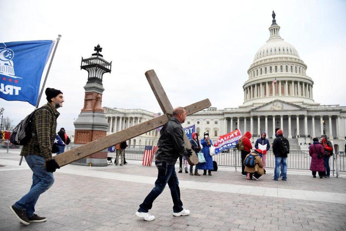 Jeremy LaPointe de Lumberton, de Texas, lleva una cruz a una protesta de partidarios de Donald Trump afuera del Capitolio. (REUTERS / Mike Theiler).