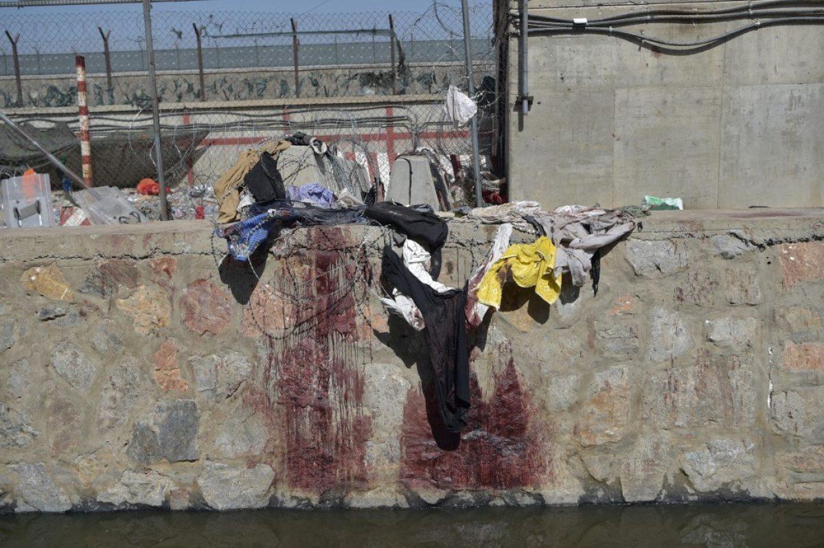 La ropa y las manchas de sangre de los afganos que esperaban ser evacuados se ven en el lugar de los dos atentados suicidas con bomba el 26 de agosto.