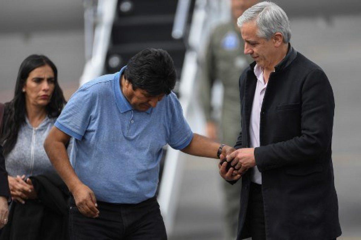 Álvaro García Linera, que renunció a la vicepresidencia de Bolivia, ayuda a Evo Morales luego de su aterrizaje en México. / AFP.