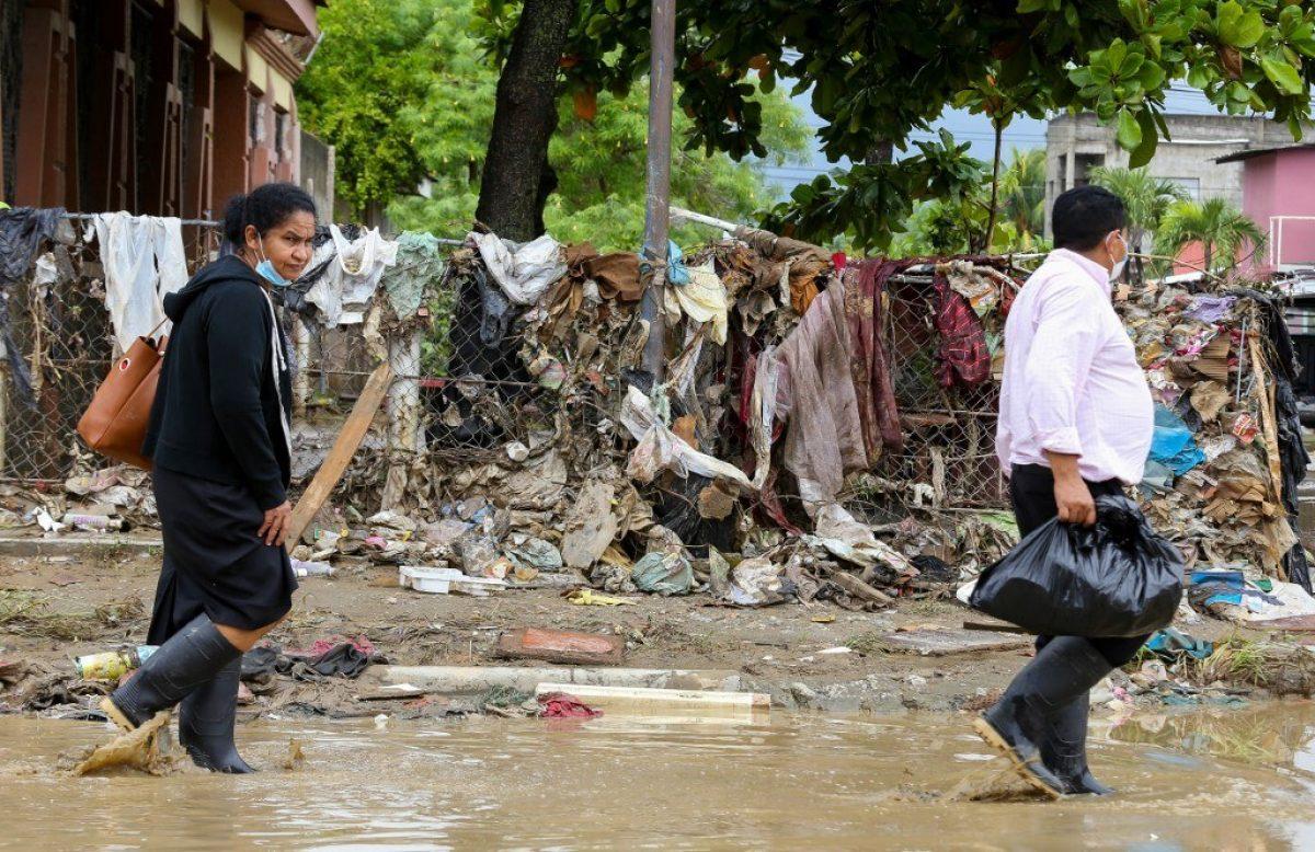 Los lugareños vadean el lodo y los escombros que dejó el desborde del río Chamelecón luego de las fuertes lluvias causadas por el huracán Iota, en Honduras.