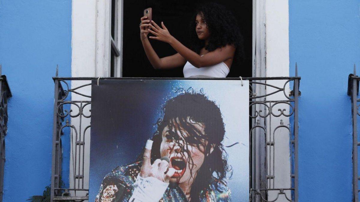 """Una joven se hace una foto en un balcón, donde se grabó el video del cantante estadounidense Michael Jackson """"They don`t care about us"""", ayer lunes, 24 de junio de 2019, en las calles de Pelourinho, en Salvador (Brasil). Michael Jackson, de cuya muerte se cumplen 10 años."""