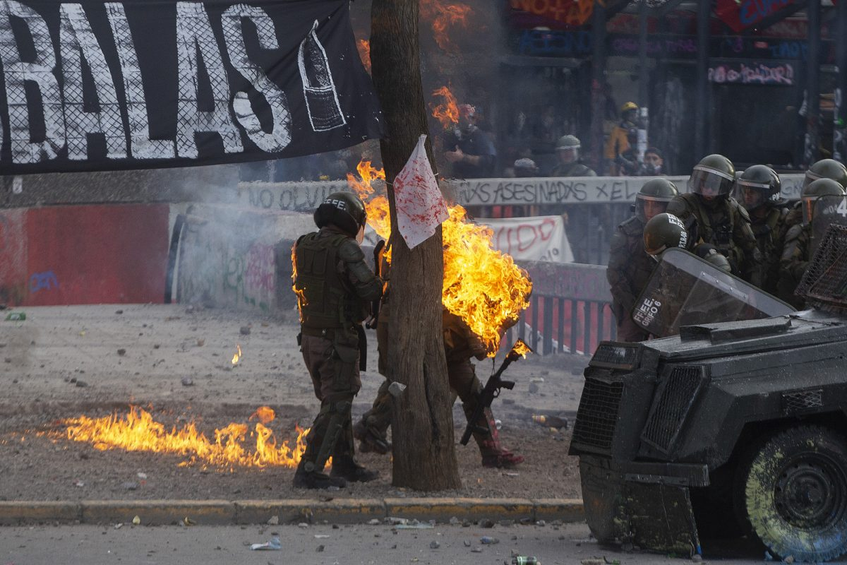Una bomba de gasolina alcanza a la policía antidisturbios durante los enfrentamientos con manifestantes que protestan contra las políticas económicas del gobierno del presidente Sebastián Piñera, en Santiago, el 4 de noviembre de 2019. (AFP)