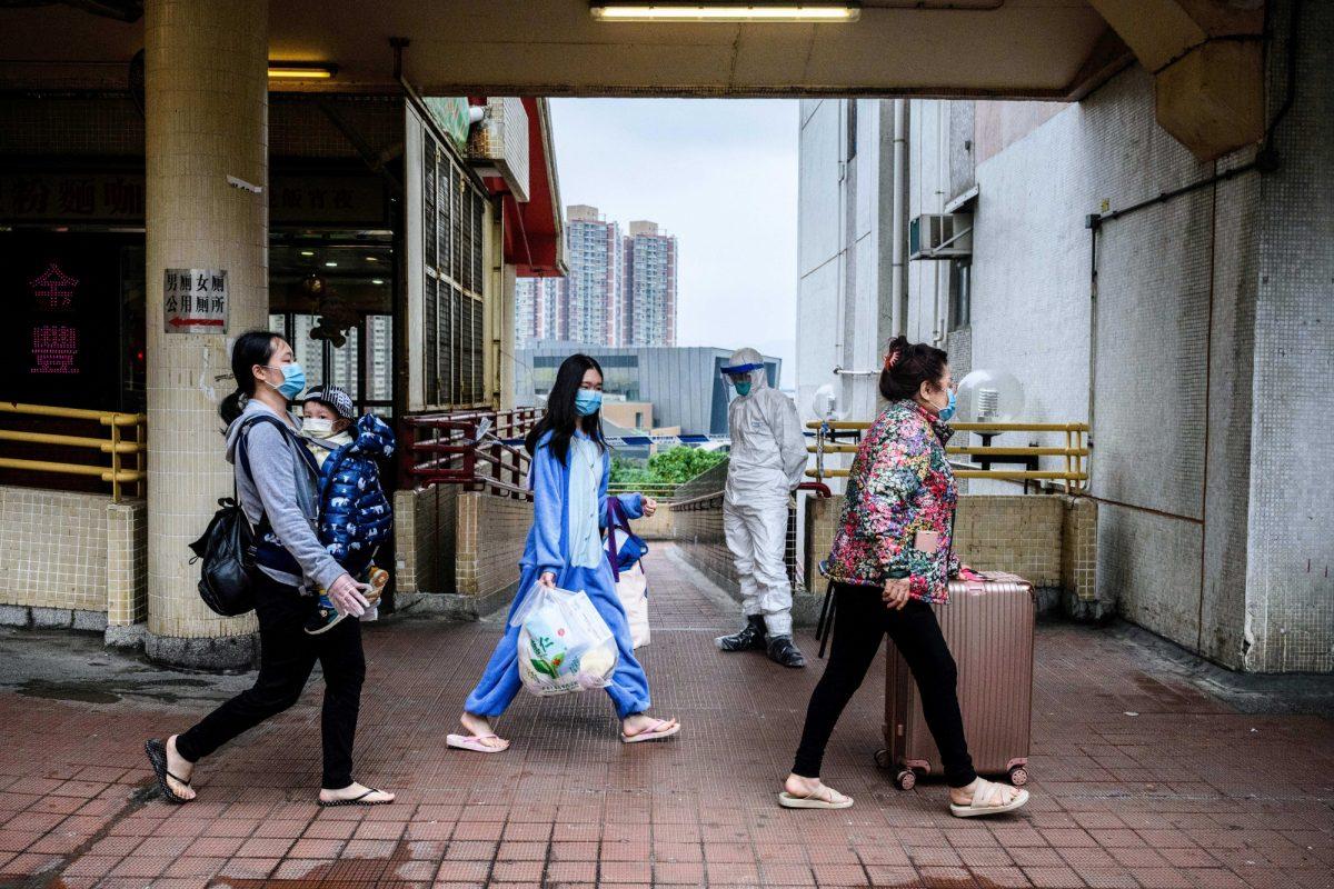 Ciudadanos caminan con máscaras faciales mientras un oficial de policía usa equipo de protección en Hong Kong (Anthony WALLACE / AFP)