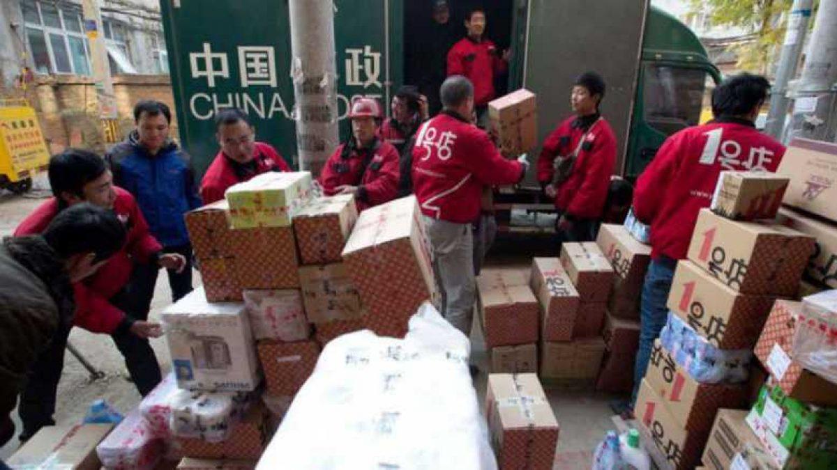 Trabajadores clasifican paquetes tras el festival de compras del Día del Soltero.